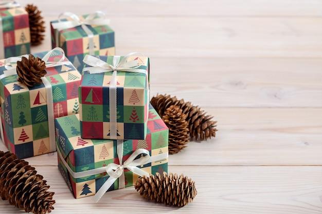 Feliz natal e feliz ano novo pinhas e presentes em papel elegante com padrão de inverno em madeira