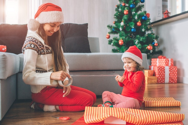 Feliz natal e feliz ano novo positiva e brincalhona jovem e garota se sentar no chão. eles sorriem e riem. criança segura parte da fita enquanto a mulher tem descanso. eles usam chapéus. meninas preparam presentes.