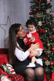 Feliz natal e feliz ano novo! retrato de uma criança emocional em um traje de ano novo com a mãe na sala decorada.