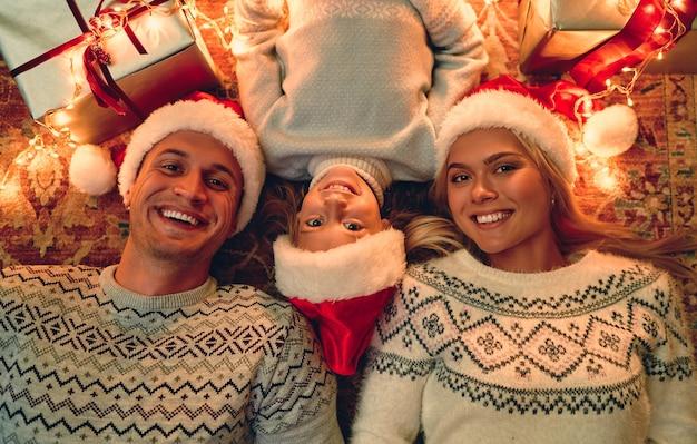 Feliz natal e feliz ano novo! vista superior da família feliz está deitada no chão com caixas de presente e uma guirlanda nas proximidades.
