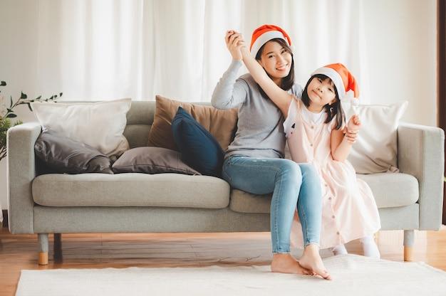 Feliz natal e feliz família asiática, mãe e filha usando chapéu de papai noel, comemorando o ano novo