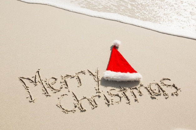 Feliz natal escrito na areia com o chapéu de santa