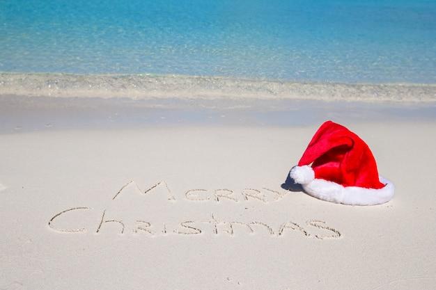 Feliz natal escrito na areia da praia tropical branco com chapéu de natal
