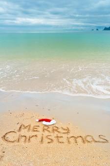 Feliz natal escrito na areia da praia tropical
