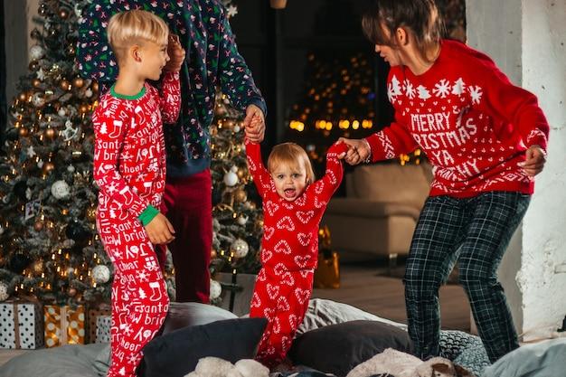 Feliz natal, família feliz, mãe, pai e filhos na cama à noite
