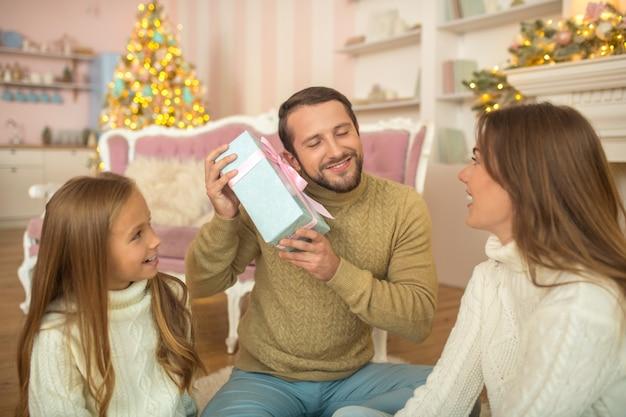Feliz natal. família jovem sentada no chão e se sentindo feliz
