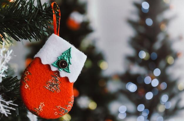 Feliz natal. fechar a cor vermelha decorado meia pendurado na árvore de natal com luzes de bokeh