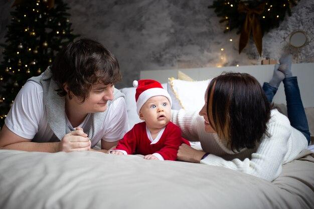 Feliz natal! feliz família mãe pai e filho na cama em casa