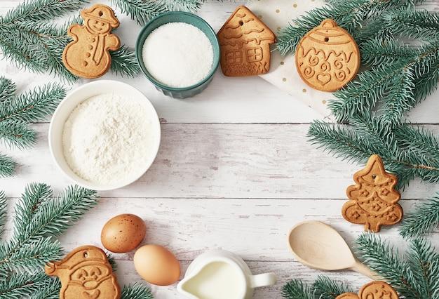 Feliz natal fundo saborosos biscoitos de gengibre caseiros. ingredientes para cozinhar, assar, utensílios de cozinha, pão de mel. cartão de feliz ano novo. mesa de natal. abeto, pinheiro.
