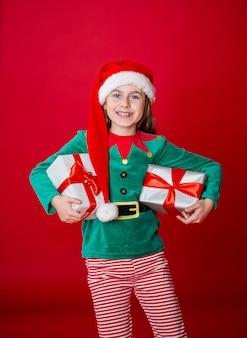Feliz natal, garota atraente feliz com presentes em uma fantasia de duende ajudante de papai noel