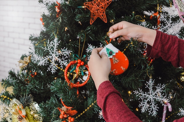 Feliz natal. jovem mão na camisola vermelha, decorando na linda árvore de natal em casa