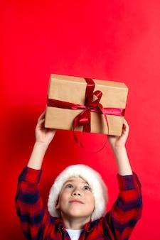 Feliz natal. menino de crianças segura uma caixa de presente amarrada com uma fita vermelha em um fundo vermelho. vertical. um lugar para texto. foto de alta qualidade