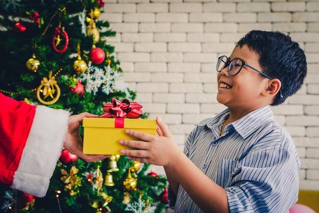 Feliz natal, menino, segurando, caixa presente, sentando, ligado, amarela, sofá, em, sala