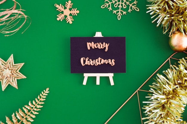 Feliz natal na vista superior do quadro-negro com coisas de ornamento de decoração de natal de ouro em verde.