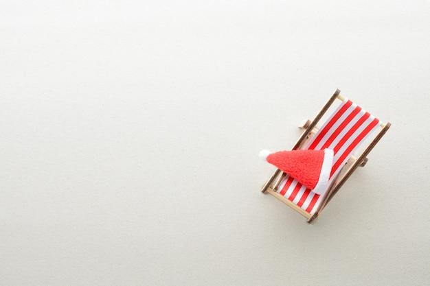 Feliz natal no conceito de praia. cadeira lounge e chapéu de papai noel. vista do topo