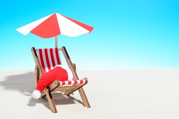 Feliz natal no conceito de praia. poltrona com guarda-chuva e chapéu de papai noel