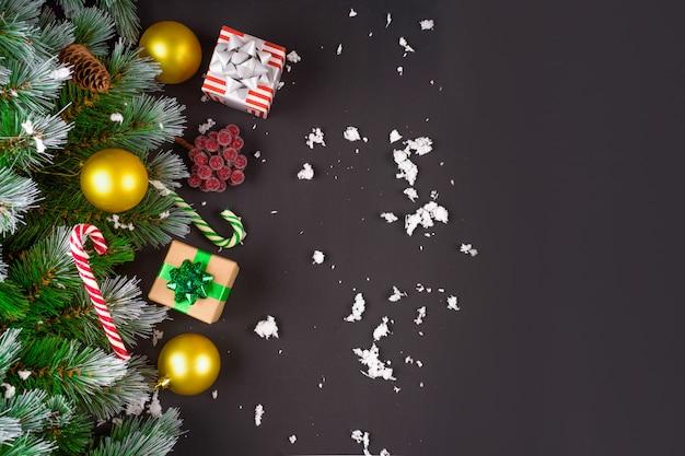 Feliz natal ou feliz ano novo quadro composição. ramos de abeto, brinquedos de natal, caixa de presente, neve fofa, pinhas, doces e bagas de inverno em fundo preto. postura plana, cópia espaço para seu texto.