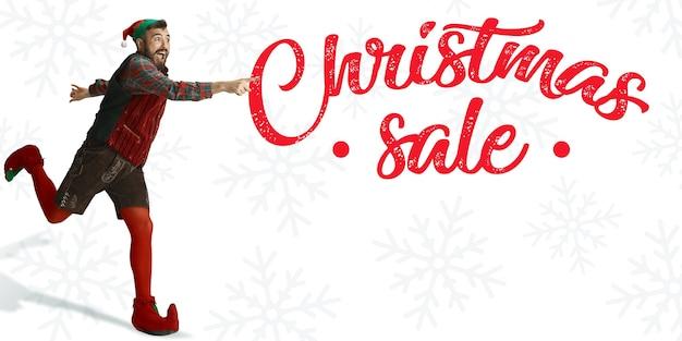 Feliz natal papai noel duende correndo e apontando no fundo branco do estúdio. modelos masculinos caucasianos em trajes tradicionais do feriado. conceito de feriados, ano novo, clima de inverno, presentes.
