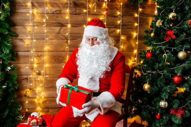 Feliz natal, papai noel perto de árvore de natal com presentes