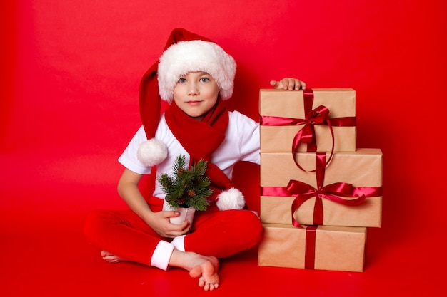 Feliz natal. retrato de um menino bonito em um boné de papai noel com caixas de presente em um fundo vermelho. um lugar para texto. foto de alta qualidade