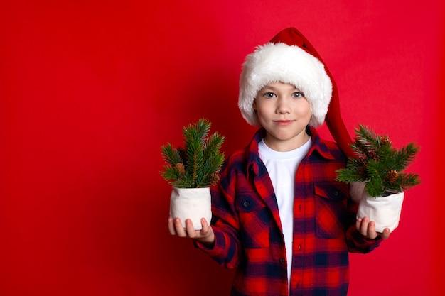Feliz natal. retrato de um menino feliz em um boné de natal com pequenas árvores de natal. fundo vermelho, espaço para texto. foto de alta qualidade