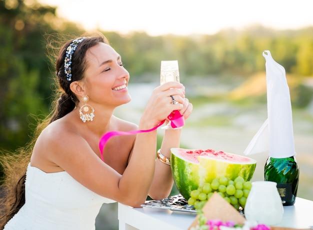 Feliz noiva jovem em um vestido branco segurando uma taça de champanhe nas mãos ao lado de uma melancia e uvas, durante uma recepção de casamento ao ar livre