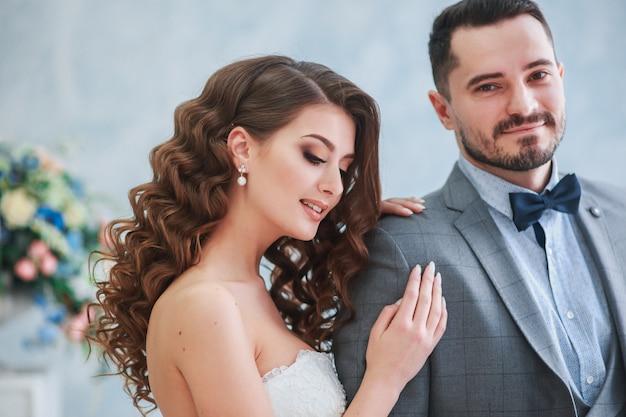 Feliz noivo e noiva posando com uma decoração de flores lindas.
