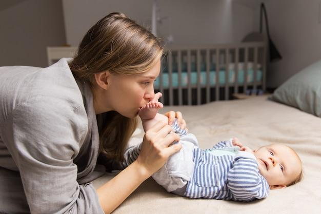 Feliz nova mãe brincalhão segurando as pernas do bebê