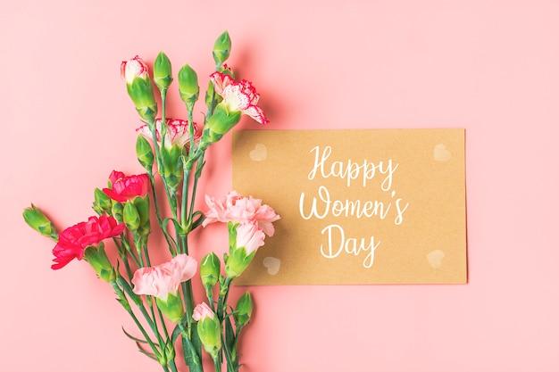 Feliz o dia da mulher. buquê colorido de diferentes flores de cravo rosa, caderno branco na superfície rosa