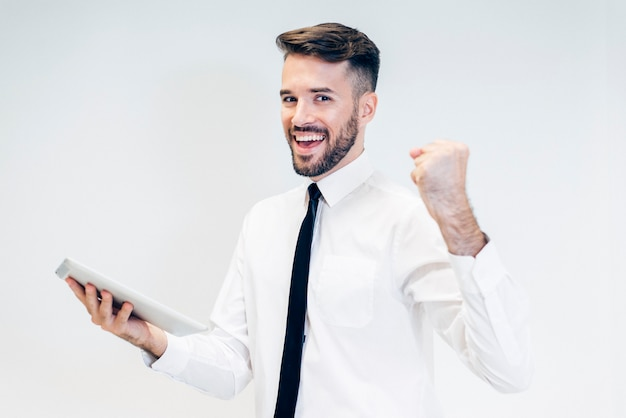 Feliz o homem a olhar para um tablet com um punho erguido