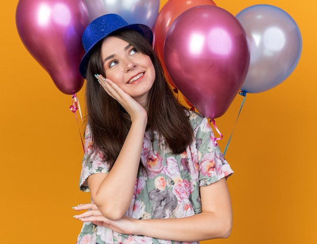 Feliz olhando para o lado, jovem e linda garota usando chapéu de festa em pé na frente de balões colocando a mão na bochecha isolada na parede laranja