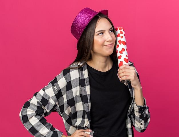 Feliz olhando para o lado, jovem e linda garota usando chapéu de festa segurando um canhão de confete e colocando a mão no quadril