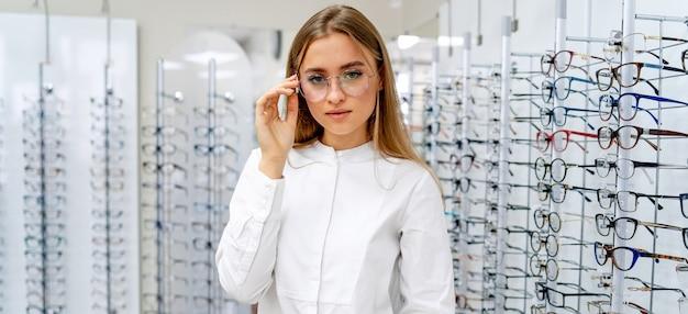 Feliz optometrista feminina, oculista está de pé com muitos copos na loja ótica.