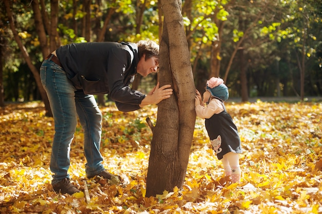 Feliz outono. pai e filha brincar de esconde-esconde