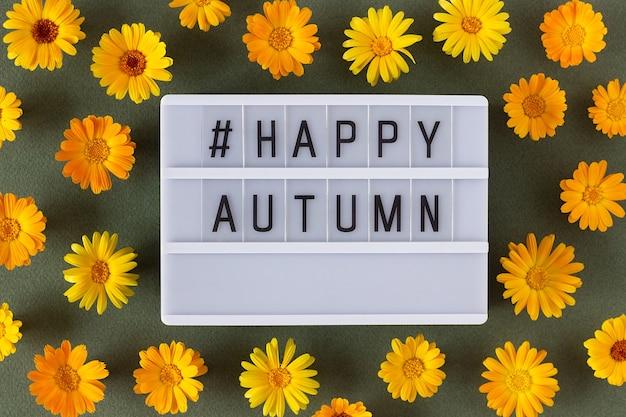 Feliz outono texto na caixa de luz e flores de calêndula laranja sobre fundo verde. vista superior flat lay minimal style. conceito bem-vindo queda. cartão de felicitações.