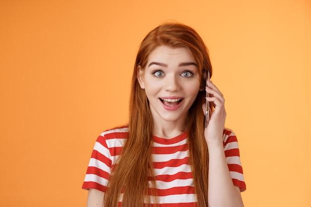 Feliz ouvir voz de amigo, ligando para o exterior. divertido surpreso menina ruiva fofa alegre pegar o telefone, segurar a orelha do smartphone, descobrir notícias incríveis, sorrir espantado, ficar com o fundo laranja animado