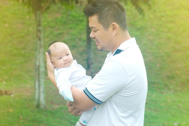 Feliz pai asiático e filho passar o tempo ao ar livre num dia de verão