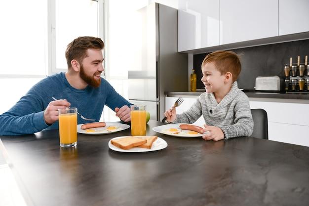 Feliz pai barbudo vestido de suéter azul comendo na cozinha com seu filho pequeno