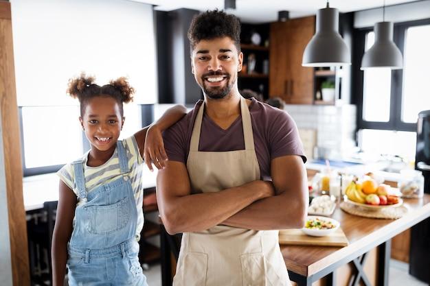 Feliz pai bonito e filhos na cozinha. comida saudável, família, conceito de cozinha
