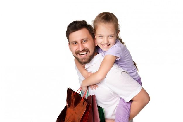Feliz pai e filha com sacos de compras em pé