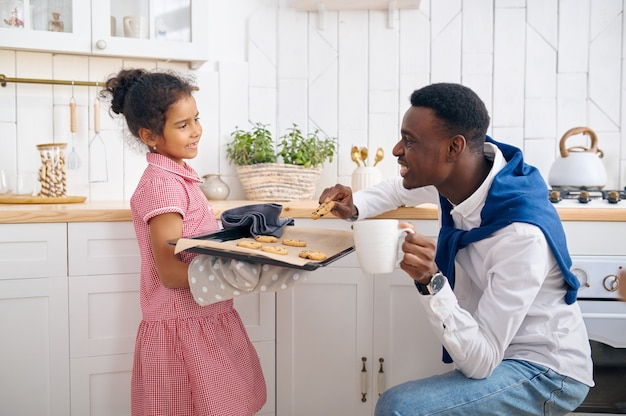 Feliz pai e filha comem bolos frescos no café da manhã. família sorridente come na cozinha pela manhã. pai alimenta criança do sexo feminino, bom relacionamento