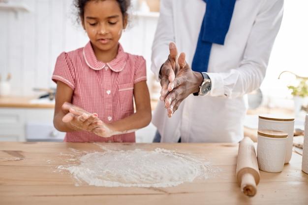 Feliz pai e filha cozinhando bolos no café da manhã. família sorridente come na cozinha pela manhã. pai alimenta criança do sexo feminino, bom relacionamento