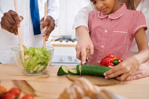 Feliz pai e filha cozinhando salada no café da manhã. família sorridente come na cozinha pela manhã. pai alimenta criança do sexo feminino, bom relacionamento