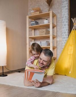 Feliz pai e filha passam algum tempo juntos em casa, lendo um livro caído no chão. a menina está deitada de costas para o pai.