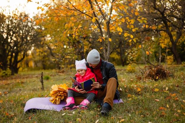 Feliz pai e filha sentado e lendo um livro no parque outono em folhas amarelas