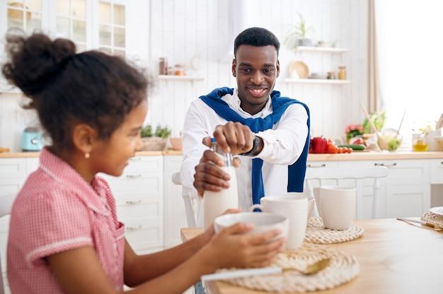 Feliz pai e filha tomando café da manhã em casa. família sorridente come na cozinha pela manhã. pai alimenta criança do sexo feminino, bom relacionamento