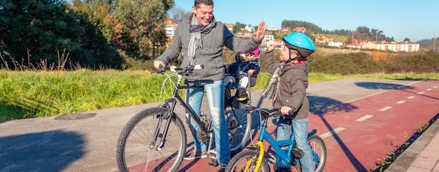 Feliz pai e filho dando cinco pelo sucesso no aprender a andar de bicicleta na cidade em um dia ensolarado de inverno. conceito de lazer ao ar livre em família.
