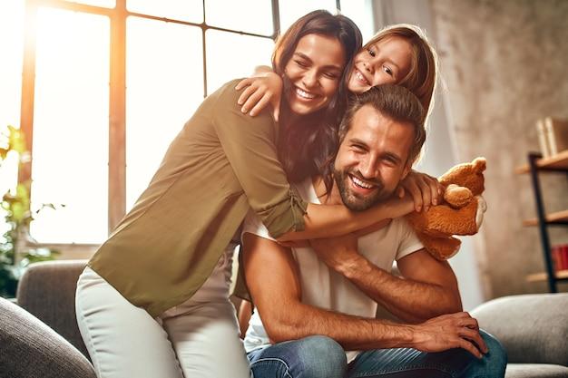 Feliz pai e mãe com sua filha fofa e ursinho de pelúcia abraçam e se divertem sentados no sofá da sala de estar em casa.