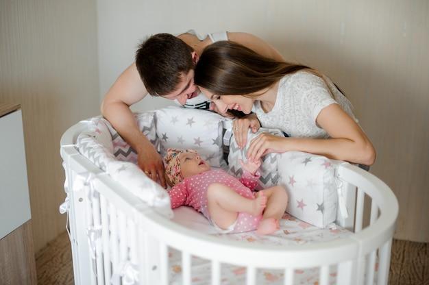 Feliz pai e mãe embalando bebê recém-nascido menina bonitinha na cama