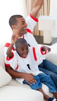 Feliz pai e seu filho comemorando um objetivo